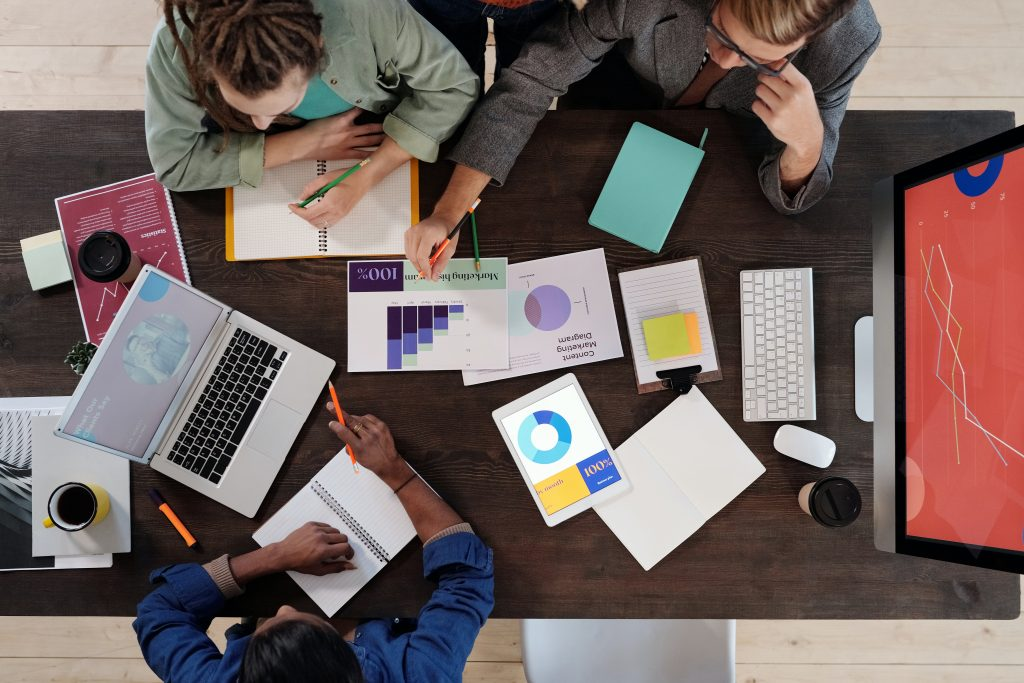 people working together on desk - concept for how to choose the right digital marketing agency